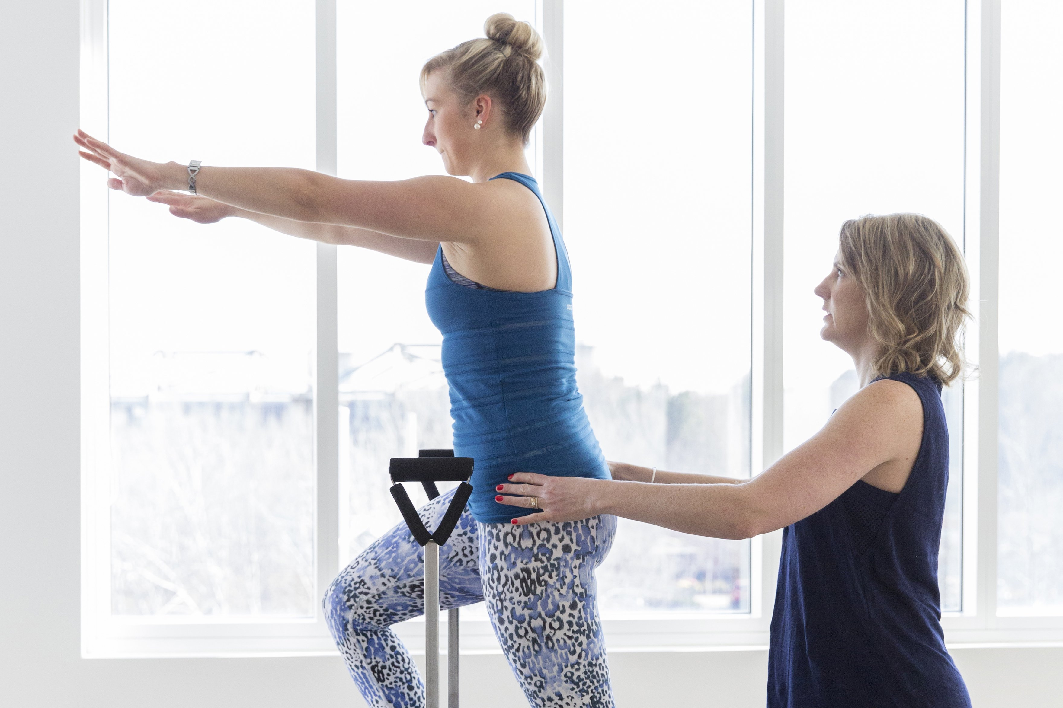 Pilates instructor helping person do Pilates